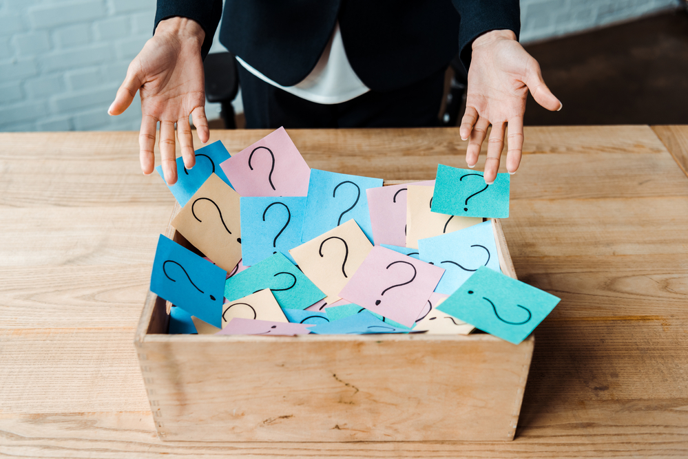 Question marks on sticky notes in a box